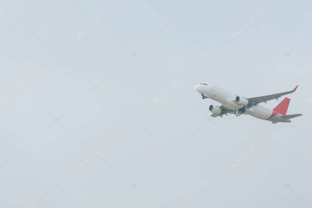 Low angle view of plane landing in cloudy sky stock vector