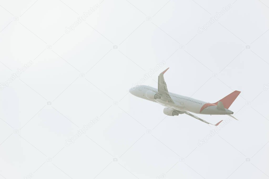 Low angle view of commercial plane taking off in cloudy sky stock vector