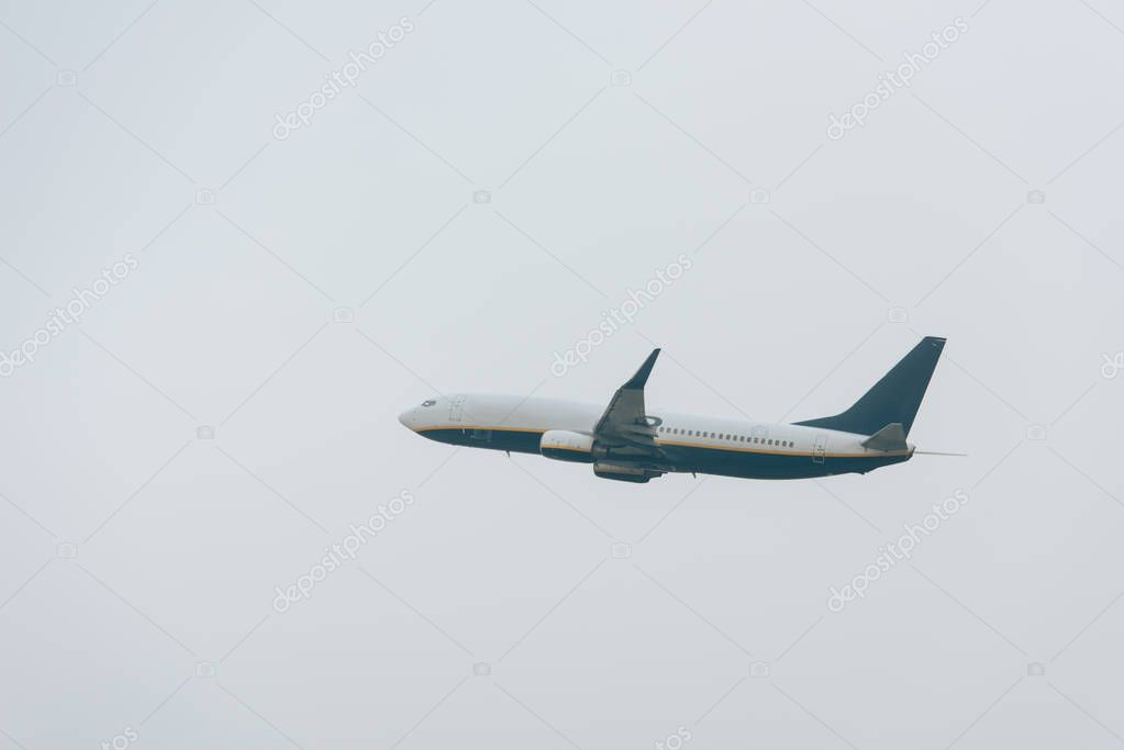 Low angle view of airplane taking off in cloudy sky stock vector