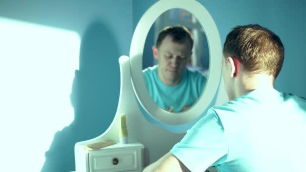 Junger Mann sitzt vor Spiegel und sprüht Parfüm auf sich