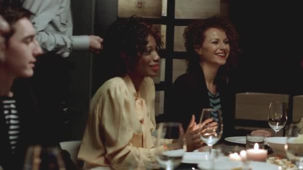 Többnemzetiségű csoport ember ül egy bárban.