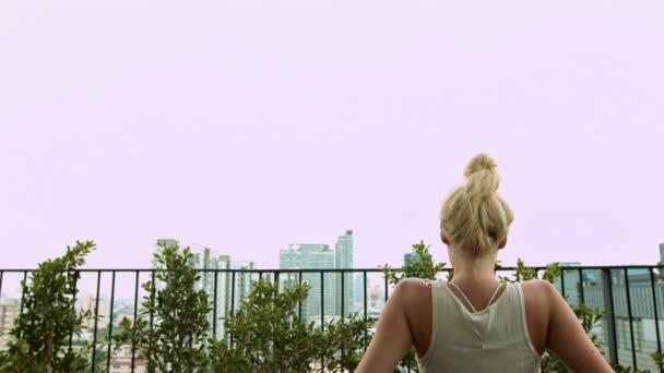 Szőke nő élvezi egy erkély