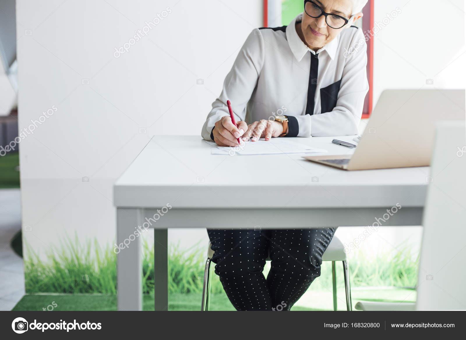 teacher grading exam papers stock photo luminastock 168320800