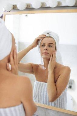 Woman Looking Herself in Bathroom Mirror