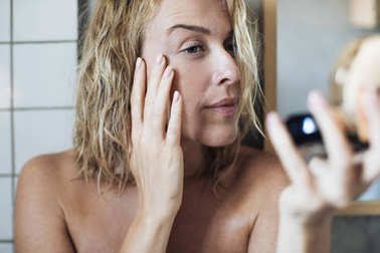 Woman Looking Herself in Mirror