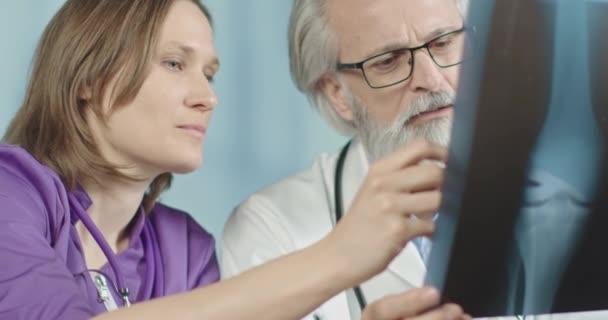 Starší lékař a mladá žena zdravotnice při pohledu na rentgen obrazu kolena