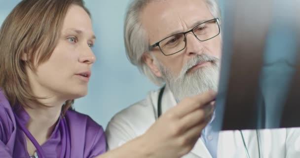 Orvos és egy nővér vizsgálja a röntgent és a CT-t a kórházban. Közepes felvétel, 4k lassított felvétel..