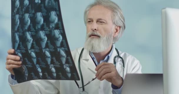 Großaufnahme eines Arztes in seinem Büro beim Betrachten von Röntgen- und CT-Scans. Coronainfektion