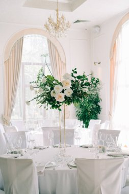 floral decoration of wedding tables, delicate white flowers and branches of fresh greenery on white hall