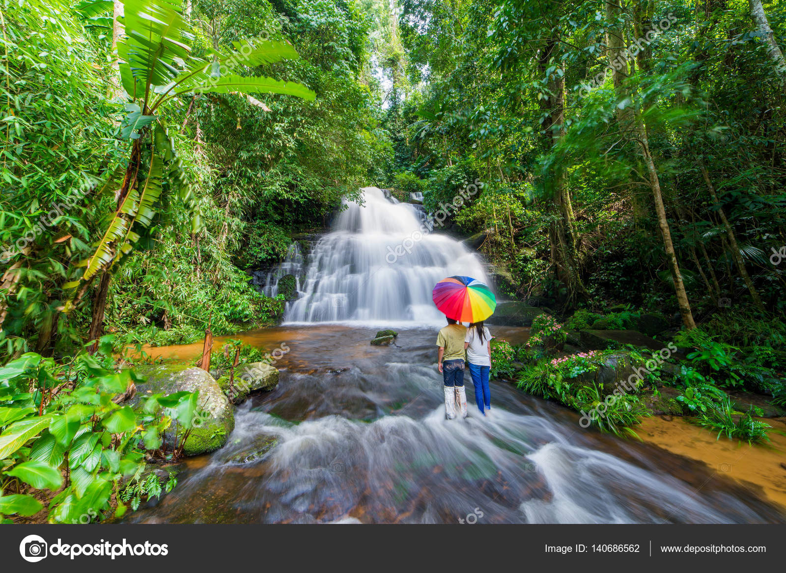Couple with colorful umbrella standing in waterfall at phu tub b ...