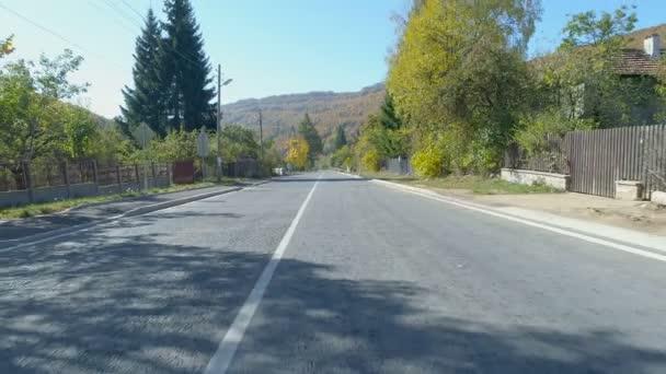 Unterwegs, Blick von der Drohne. Ruhige Asphaltstraße in bulgarischem Dorf im Herbst
