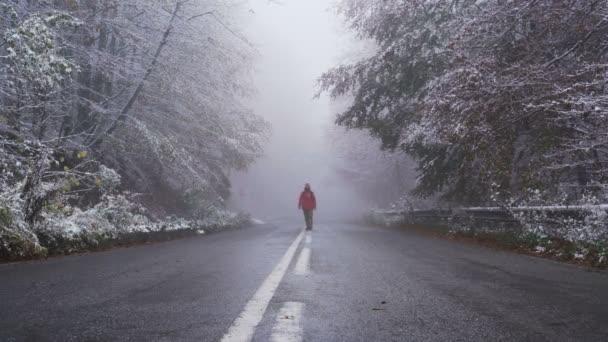 Männlicher Tourist mit leuchtend roter Jacke läuft mit weit aufgerissenen Armen auf Asphaltstraße