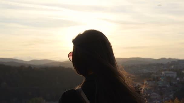 Mädchenhaare wehen im Wind, während sie den schönen Sonnenuntergang genießt