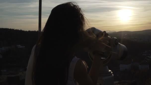 Mädchen mit vom Wind verwehten Haaren beobachtet den Sonnenuntergang über Veliko Tarnovo mit Fernglas