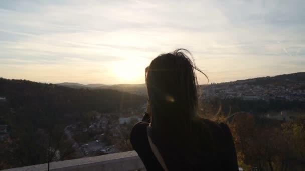 Mädchen mit Sonnenbrille genießt den Sonnenuntergang über der malerischen Landschaft, während Wind in ihre Haare bläst