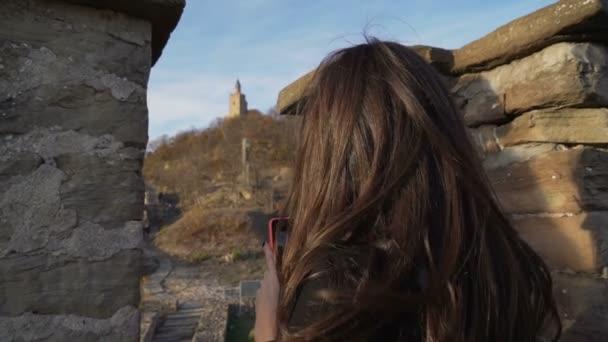 junge Frau mit schönen braunen Haaren, die im Urlaub Fotos mit ihrem Handy macht