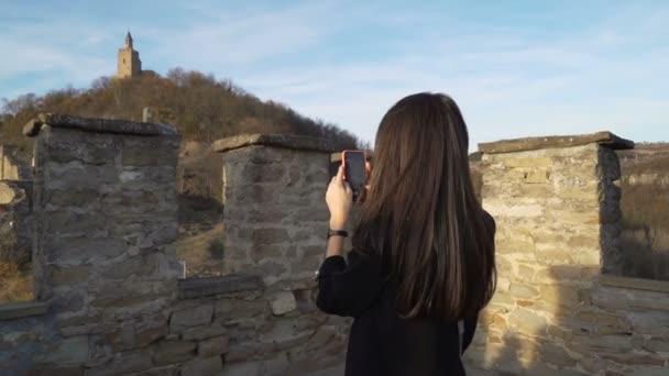 Mädchen mit langen braunen Haaren beim Urlaub in Zarevets, Veliko tarnovo. Fotos mit dem Smartphone machen