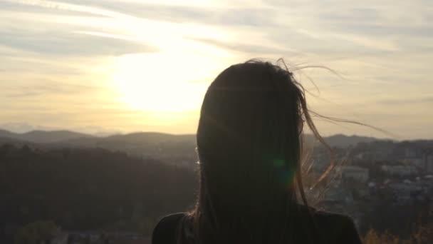 Wind weht Mädchen Haare, während sie den Sonnenuntergang über den Hügeln beobachtet