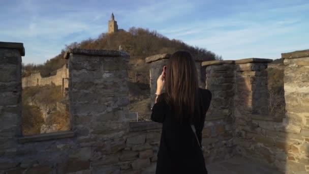 brünettes Mädchen mit schwarzer Jacke genießt den sonnigen Herbsttag in der alten mittelalterlichen Festung namens Zarevets in Bulgarien