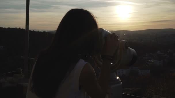Brünettes Mädchen beobachtet die Stadt mit Ferngläsern auf dem Zarevets-Hügel in Veliko tarnovo