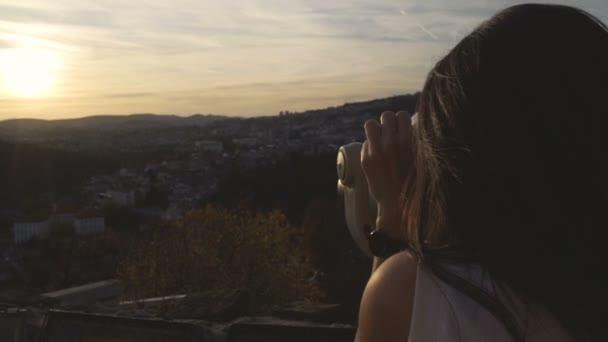 Nahaufnahme einer Frau, die mit dem Fernglas den Sonnenuntergang über Häusern auf den Hügeln in Veliko tarnovo beobachtet