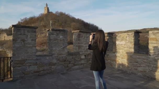 Frau mit schwarzer Jacke fotografiert alte mittelalterliche Festung in Veliko tarnovo
