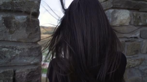 Brünettes Mädchen schaut durch mittelalterliche Festungsmauer und fotografiert mit Smartphone