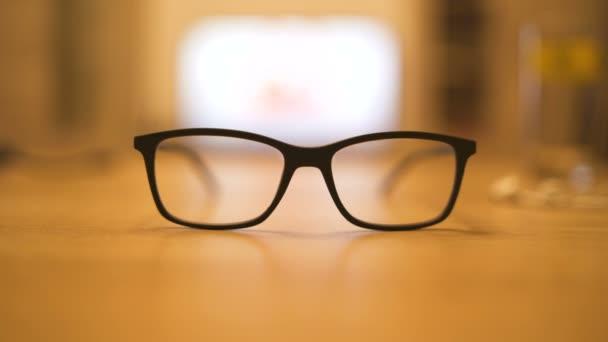 Černé brýle na kuchyňském stole. Televizní obrazovka viděl koryta brýle