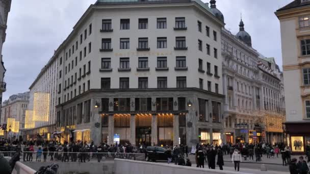 City center old town with shops and restaurants full of people with christmas decorations lights cars horses at day time in Vienna Austria December 2018