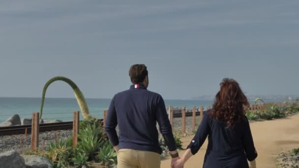 Happy Couple Enjoying Beautiful Day Walking holding hands on the Beach. CLose to Pacific surfliner rails Travel Vacation Retirement Lifestyle Concept California Orange county San clemente