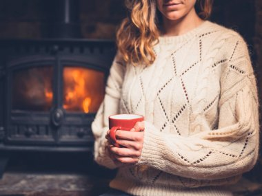 A young woman in a white jumper is sitting by the fireplace drinking from a mug stock vector