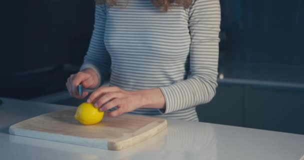 Egy fiatal nő citromot vág a konyhájában.
