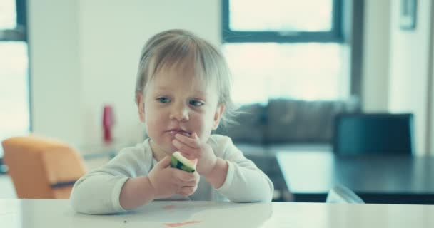 A cute little toddler boy is eating watermelon at home in a city apartment