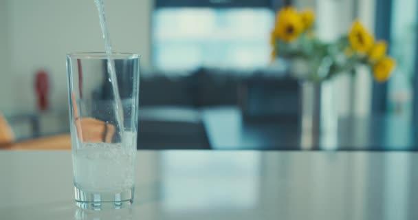 Voda se nalévá do sklenice v městské kuchyni v reálném čase
