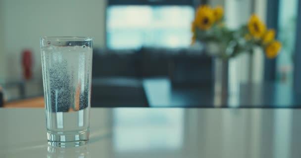 Sklenice perlivé vody stojí na kuchyňské lince ve městě a bublá
