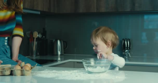 A little toddler boy is in the kitchen with his mother and is stirring a bowl of flour with a wooden spoon