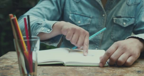close-up footage of man drawing in sketchbook with colored pencils