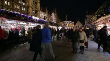 Munich, Germany - December 8, 2015: view of buldings with festive lighting and busy people walking on the street