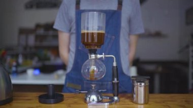 young man preparing coffee with Syphon Vacuum Coffee Maker