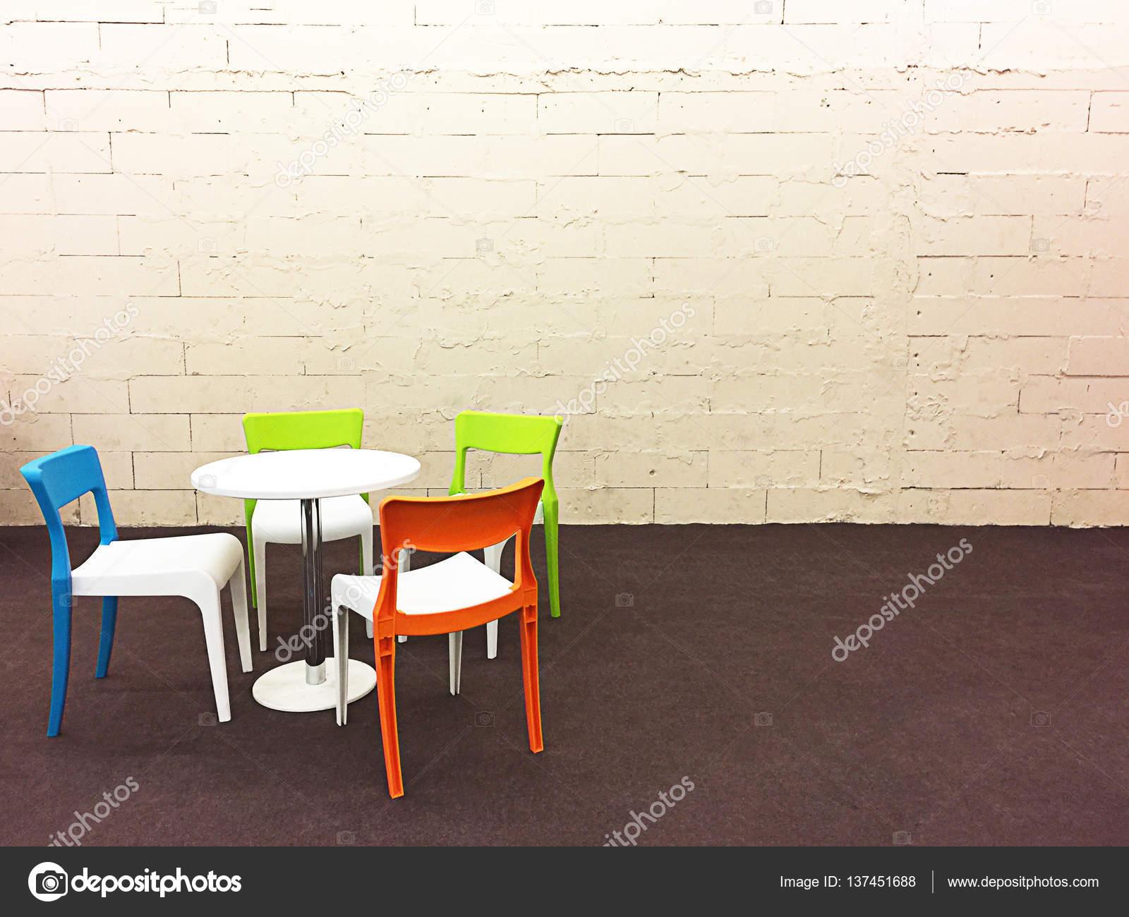 Sedie moderne colorati sulla parete bloccano tappeto crema e