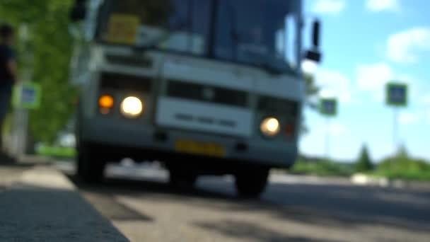 Veřejný autobus příjezd na autobusové zastávce v provinčním městě. Cestující nastupují do autobusu. Autobus odjíždí na trasu. Rozmazané pozadí. Zavřít snímek