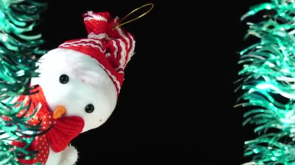 Roztomilý sněhulák v červeném klobouku a luk se dívá na vás ze scény. Vánoční pozdrav na černém pozadí. Slavnostní nálada. Nový rok nebo téma svátků