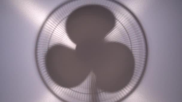 A háztartási ventilátor sziluettje lelassul és megáll. Elektromos padlóventilátor léghűtéshez. Videó a fény háttér