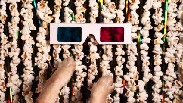 Cats paw plays with 3D glasses. Defocused dynamic background of garlands from popcorn and golden sparkling tinsel. Comic news, funny entertainment, fun. 4K video