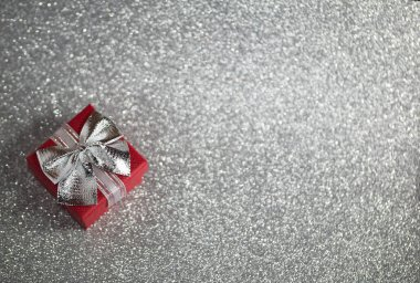 Red gift box with silver bow on silver glitter surface with bokeh lights.