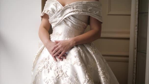 nevěsta v šatech se vzory představuje stojící v blízkosti parapetu