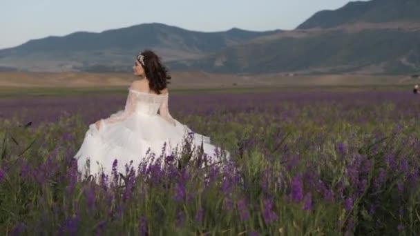 nevěsta v elegantních šatech s bujnou sukní ve fialových květinách