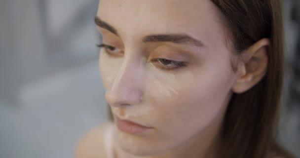 skilled makeup artist applies concealer on model face