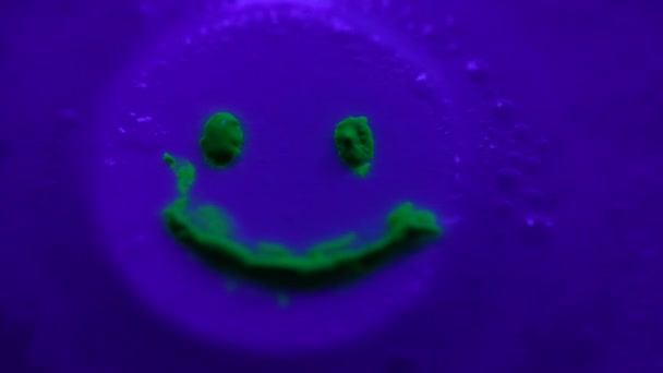 dissolving tablet with green neon smile in water with foam