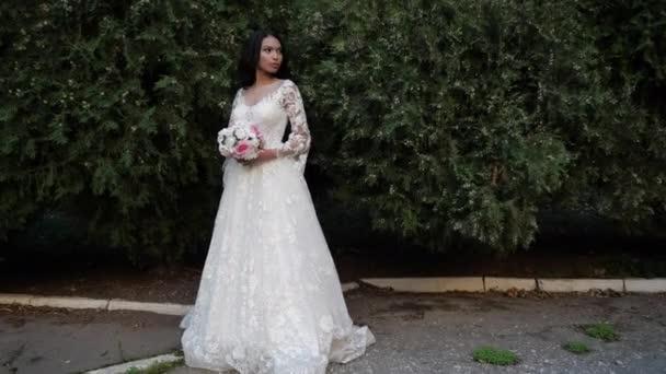 vonzó hölgy esküvői ruha tartja virágok közelében bokrok